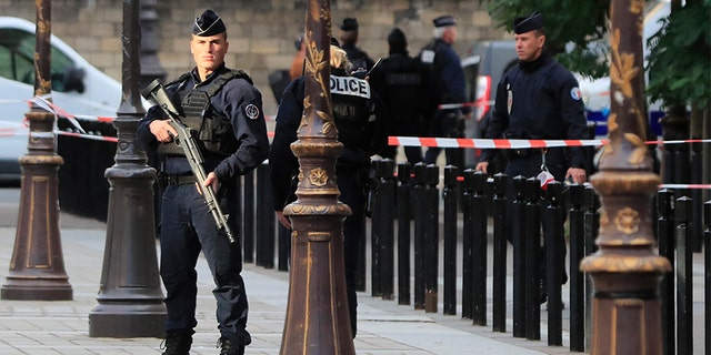 Police officers control the perimeter outside the Paris police headquarters on Thursday after an administrator armed with a knife attacked officers inside. (AP)