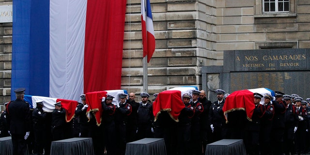 The four victims of last week's knife attack at the Paris police headquarters were posthumously given France's highest award, the Legion of Honor. (AP Photo/Francois Mori)