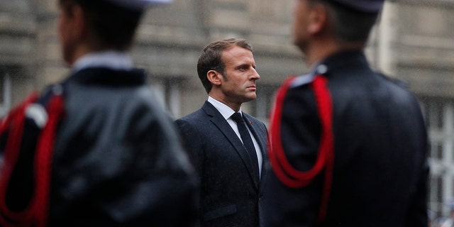 French President Emmanuel Macron stands at attention by the coffins of the four victims of last week's knife attack in the courtyard of the Paris police headquarters during a ceremony, Tuesday, Oct. 8, 2019 in Paris. France's presidency says the four victims of last week's knife attack at the Paris police headquarters will be posthumously given France's highest award, the Legion of Honor. (AP Photo/Francois Mori, Pool)