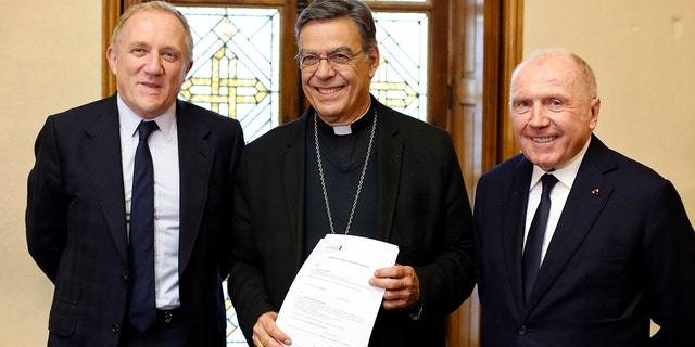 Francois-Henri Pinault, left, his father Francois Pinault, right, and Archbishop of Paris Michel Aupetit, center, pose after signing an agreement to raise money for the rebuilding of Notre-Dame cathedral. (AP Photo/Thibault Camus)