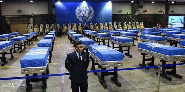 A U.S. airman stands guard next to caskets containing remains of U.S. soldiers killed in the Korean War and collected in North Korea before a repatriation ceremony at Osan Air Base in Pyeongtaek, South Korea, in August 2018.