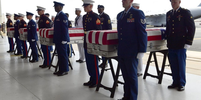 Military members stand at attention after placing transfer cases in a hanger at a ceremony marking the arrival of the remains believed to be of American service members who fell in the Korean War at Joint Base Pearl Harbor-Hickam in Hawaii, in August 2018. (AP)