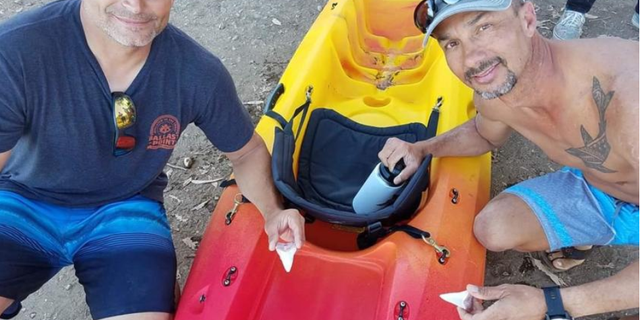 Bill Powers, left, and Danny McDaniel each hold a great white's tooth lost when the shark bit into McDaniel's kayak. <br>