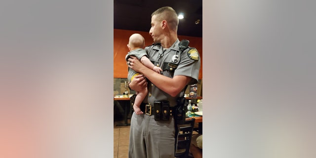 """Kentucky State Trooper Aaron Hampton is being praised as a """"fantastic officer"""" and """"awesome gentleman"""" for holding a fussy baby in a restaurant so the youngster's mother could have a moment to eat in peace."""