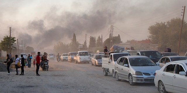 Syrians flee shelling by Turkish forces in Ras al-Ayn, northeast Syria on Wednesday.