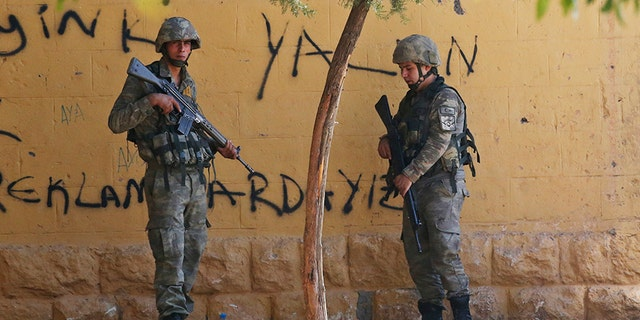 Turkish soldiers stand at the border with Syria in Akcakale, Sanliurfa province, southeastern Turkey, on Thursday.