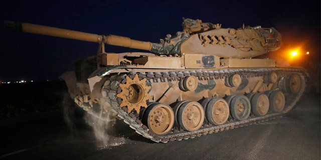 A Turkish Army tank is driven to its new position, on the Turkish side of the border between Turkey and Syria, in Sanliurfa province, on Tuesday.