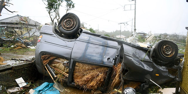 An overturned automobile lies on a belligerent following a clever breeze in Ichihara, Chiba, nearby Tokyo Saturday, Oct. 12, 2019. Under murky skies, a hurricane ripped by Chiba on Saturday.(Kyodo News around AP)