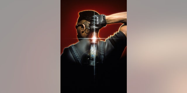 """Wesley Snipes holds a katana behind his back in a scene from the film """"Blade"""" in 1999."""