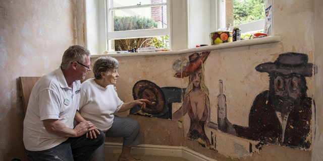 "David Parton a staff member at Stokeleigh Care Home who discovered a series of paintings believed to date back to World War II shows them to Jan, a resident at the Care Home. Due to the picture's ""racy"" nature, it is believed the room may have been used as a gentlemen's lounge. (Credit: SWNS)"