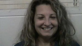 Oklahoma woman, 48, smiles in mugshot after arrest in husband's stabbing death