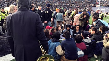 Climate protesters delay Harvard-Yale football game after staging sit-in on field