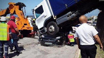 South African woman survives after truck rolls down hill and lands on her car, trapping her