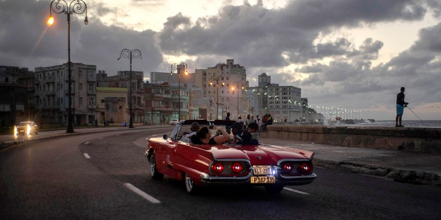 In this Nov. 10, 2019, photo, tourists take a joy ride along the malecon sea wall in Havana, Cuba. The city of Havana celebrated its 500th anniversary on Nov. 16. (AP Photo/Ramon Espinosa)