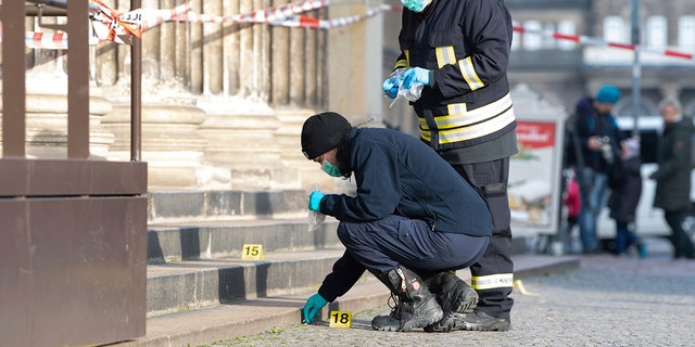 Police officers work behind a caution tape at the Schinkelwache building in Dresden Monday, Nov. 25, 2019.  (Sebastian Kahnert/dpa via AP)