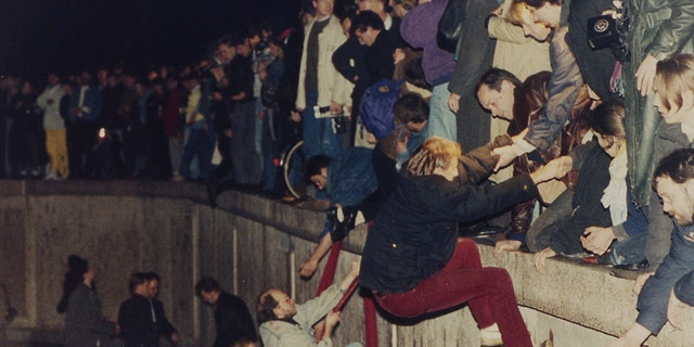 People climbing the Berlin Wall which had divided the city since the end of World War II, near the Brandenburg Gate, on Nov. 10, 1989. (AP Photo/Jockel Finck, File)