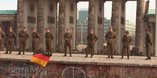 East German border guards standing on top of the Berlin wall in front of the Brandenburg Gate on Nov. 11, 1989.(AP Photo/Lionel Cironneau, File)