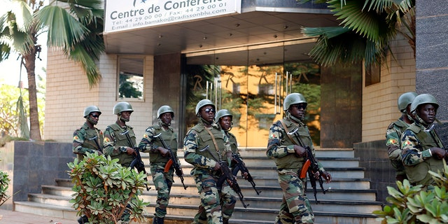 In this Saturday, Nov. 21, 2015 file photo, soldiers from the presidential guard patrol outside the Radisson Blu hotel in Bamako after it was attacked by Islamic extremists armed with guns and grenades.