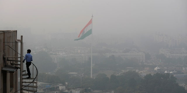 An Indian walks up to the stairs as Delhi's skyline is seen enveloped in smog and dust in New Delhi, India, Friday, Nov. 1, 2019. (AP Photo/Manish Swarup)