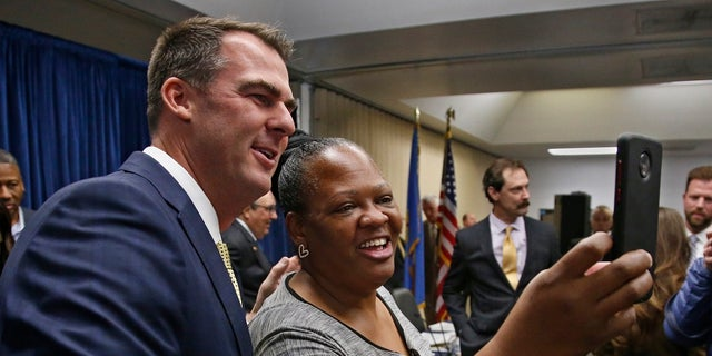 Oklahoma Gov. Kevin Stitt, left, poses for a selfie with Joy Block, right, of Tulsa, Okla., following a news conference Friday to announce that Oklahoma will release more than 400 inmates after the board approved what they say is the largest single-day mass commutation in U.S. history. (AP Photo/Sue Ogrocki)