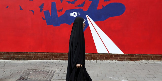 A woman walks past a new anti-U.S. mural on the wall of former U.S. embassy portraying the interception of Global Hawk US drone by Iran in Persian Gulf, after an unveiling ceremony in Tehran, Iran, Saturday, Nov. 2, 2019. (AP Photo/Vahid Salemi)