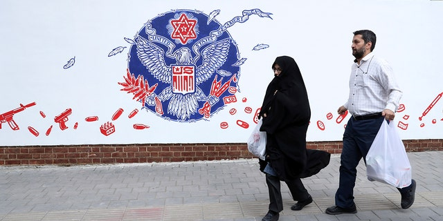 People walk past a satirical drawing of the Great Seal of the United States after new anti-U.S. murals on the walls of former U.S. embassy unveiled in a ceremony in Tehran, Iran, Saturday, Nov. 2, 2019. (AP Photo/Vahid Salemi)