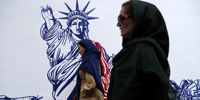 People walk past a satirical drawing of Statue of Liberty after new anti-U.S. murals on the walls of former U.S. embassy unveiled in a ceremony in Tehran, Iran, Saturday, Nov. 2, 2019. (AP Photo/Vahid Salemi)
