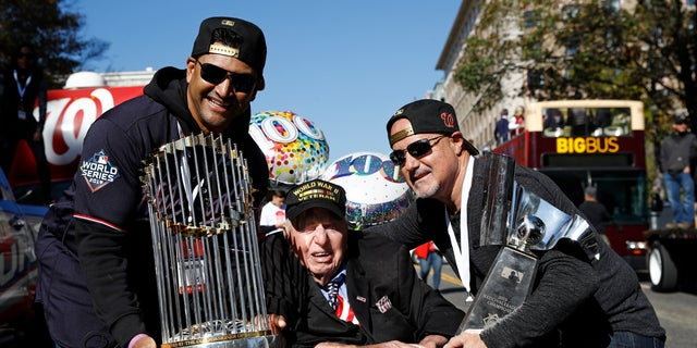 Washington Nationals manager Dave Martinez, left, and general manager Mike Rizzo, right, pose with Sidney Walton, age 100, after showing him the World Series and NLCS trophies before a parade to celebrate the team's World Series baseball championship over the Houston Astros, Saturday, Nov. 2, 2019, in Washington. (AP Photo/Patrick Semansky)