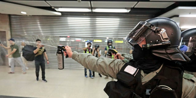 A riot police officer fires pepper spray toward people at a shopping mall in Hong Kong, Sunday, Nov. 3, 2019. Riot police stormed several malls in Hong Kong on Sunday in a move to thwart more pro-democracy protests, as the city's leader heads to Beijing for talks on deepening economic integration between the semi-autonomous Chinese territory and mainland China. (AP Photo/Dita Alangkara)