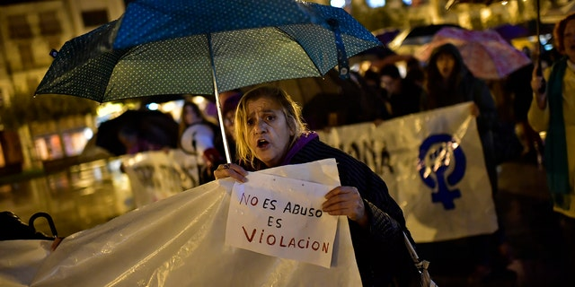 A woman holds a sign reading ''It is not abuse, it is rape'' as people gather at Plaza del Castillo square to a protest against sexual assault, in Pamplona, northern Spain, Monday, Nov. 4, 2019.  (AP Photo/Alvaro Barrientos)
