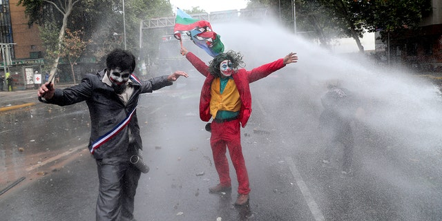 """Men dressed as clowns, one dressed as the the movie character """"The Joker"""" flying a Mapuche indigenous flag, are sprayed by a police water cannon during an anti-government protest in Santiago, Chile, Monday, Nov. 4, 2019."""
