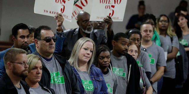 """People wearing """"Save The Paseo"""" shirts stand among attendees at a rally to keep a street named in honor of Dr. Martin Luther King Jr. at the Paseo Baptist Church in Kansas City, Mo., Nov. 3, 2019. (Associated Press)"""