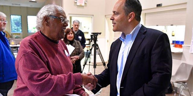 Kentucky Governor and Republican gubernatorial candidate Matt Bevin, right, shakes hands with a poll worker after casting his ballot in the state's general election in Louisville, Ky., Tuesday, Nov. 5, 2019. (AP Photo/Timothy D. Easley)