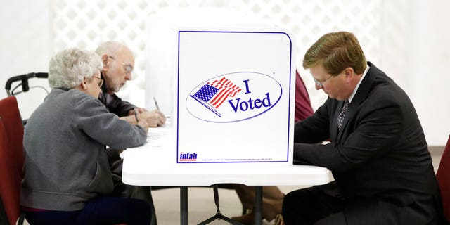 Republican nominee for governor and current Lt. Gov. Tate Reeves, right, joins other registered voters in voting at his Flowood, Miss., precinct, Tuesday Nov. 5, 2019. Voters are having their say in Mississippi's most hotly contested governor's race since 2003. They are also selecting six other statewide officials and deciding a host of legislative and local offices. (AP Photo/Rogelio V. Solis)