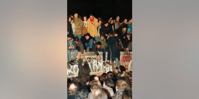 In this Saturday Nov. 11, 1989 file photo, hundreds of Berliners climb on top of the Berlin Wall at Brandenburg Gate in Berlin, demanding in a peaceful protest that the wall will be pulled down.