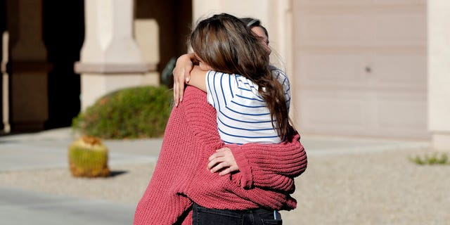 Madelyn Staddon, reg, a relative of some of the members of a Mormon community who were attacked while traveling near the US-Mexico border, embraces a neighbor outside her home, Dinsdag, Nov.. 5, 2019, in Queen Creek, Ariz. Drug cartel gunmen ambushed three vehicles along a road near the state border of Chihuahua and Sonora on Monday, slaughtering at least six children and three women from the extended LeBaron family, all of them U.S. citizens living in northern Mexico, authorities said Tuesday. (AP Photo/Matt York)