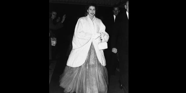 In this Nov. 28, 1952 file photo, Queen Elizabeth II, wearing an ermine coat over her full-skirted evening dress, arrives at Royal Festival Hall in London for a concert. (AP Photo, File)