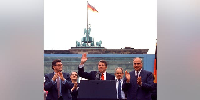 In this on Friday, June 12, 1987 file photo, U.S. President Ronald Reagan acknowledges the applause after speaking to an audience in front of the Brandenburg Gate in Berlin. Beside Reagan are the President of the German Parliament Philipp Jenninger, left, and Germany's Chancellor Helmut Kohl, right.