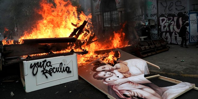 Items removed from a church by anti-government protesters go up in flames in a barricade built by the protesters in Santiago, Chile on Friday. (AP Photo/Esteban Felix)