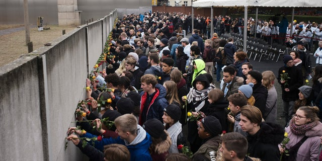 Young people stuck flowers in remains of the Berlin Wall during a commemoration ceremony to celebrate the 30th anniversary of the fall of the Berlin Wall at the Wall memorial site at Bernauer Strasse in Berlin, Saturday, Nov. 9, 2019.