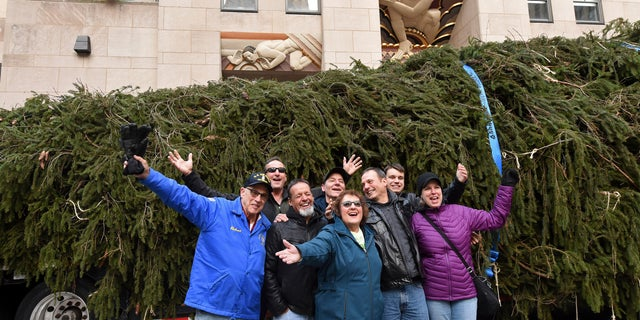 Carol Schultz, center, donor of this year's Rockefeller Center Christmas tree, poses with her family in front of her 77-foot tall Norway Spruce she donated to serve as the 2019 Rockefeller Center Christmas tree.