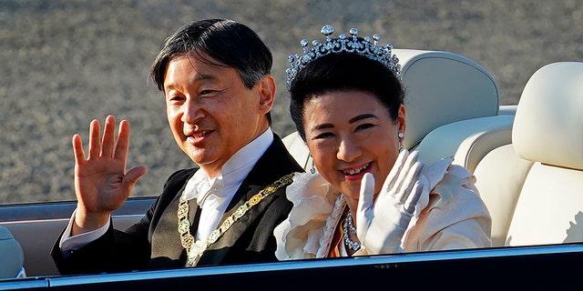 Japanese Emperor Naruhito, left, and Empress Masako, right, wave during the royal motorcade in Tokyo, Sunday, Nov. 10, 2019. (Associated Press)