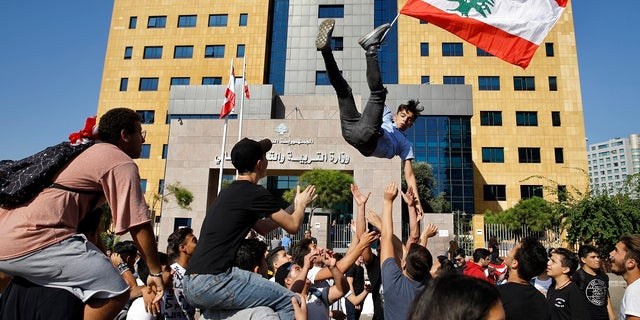 A student protester is thrown into the air by his colleagues in front of the education ministry in Beirut on Tuesday. (AP Photo/Bilal Hussein)