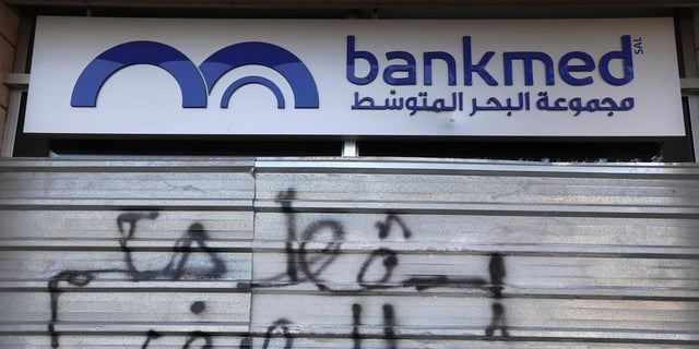 "Graffiti in Arabic reads ""Down with the rule of the banks,"" on the front of a closed bank building in Beirut Tuesday. (AP Photo/Hassan Ammar)"