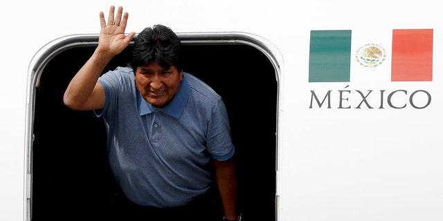 Morales waves upon arrival to Mexico City, Tuesday, Nov. 12, 2019. (AP Photo/Eduardo Verdugo)