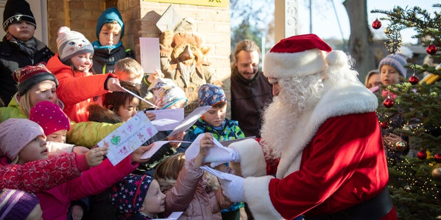 A man dressed as Santa Claus is welcomed by children during the opening of the most famous German Christmas mail office in the small village of Himmelpfort north of Berlin, Germany. (Soeren Stache/dpa via AP)