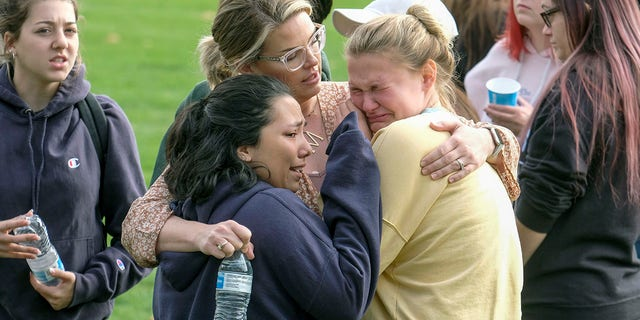 Students are comforted as they wait to be reunited with their parents following a shooting at Saugus High School that injured several people on Thursday in Santa Clarita, Calif. (AP Photo/Ringo H.W. Chiu)