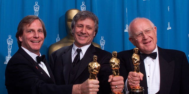 """From left: Douglas Wick, David Franzoni and Branko Lustig hold their Oscars backstage at the Shrine Auditorium in Los Angeles, after """"Gladiator"""" was honored as best picture of the year by the Academy of Motion Pictures Arts & Sciences."""