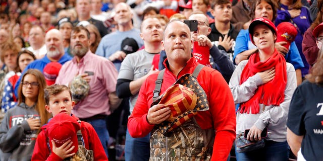A man and boy dressed in chest waders holding their hats to their hearts during the Pledge of Allegiance at the start of the rally Thursday. (AP Photo/Gerald Herbert)