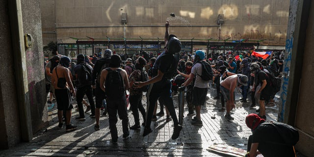 Anti-government demonstrators clash with police during a protest in Santiago, Chile, Thursday, Nov. 14, 2019. Students in Chile began protesting nearly a month ago over a subway fare hike. The demonstrations have morphed into a massive protest movement demanding improvements in basic services and benefits, including pensions, health, and education. (AP Photo/Esteban Felix)